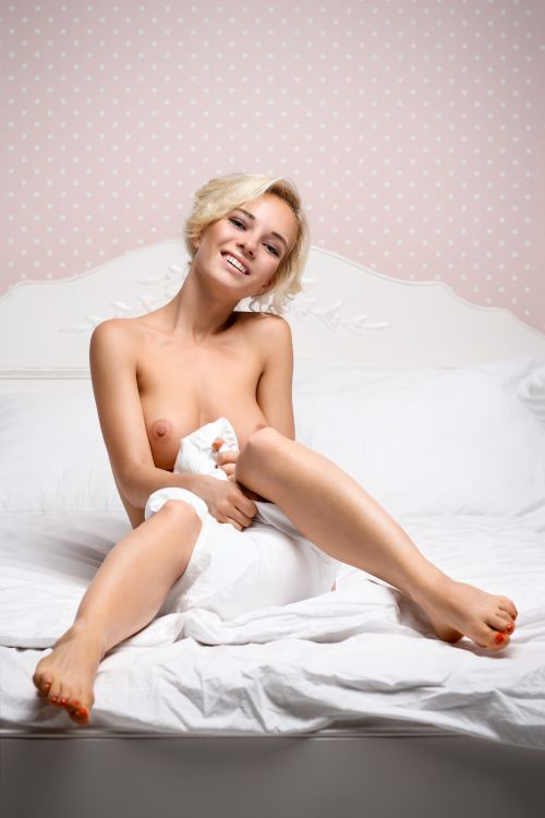 naked blonde girl sitting in her bed lascivious