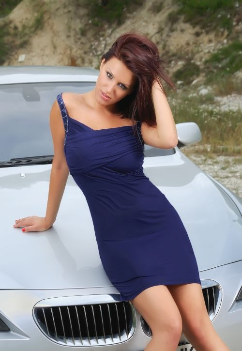 sexy redhead in a blue dress in front of a sport car