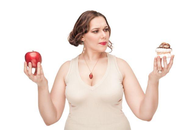 mollige Frau hält Apfel in der einen und Kuchen in der anderen Hand