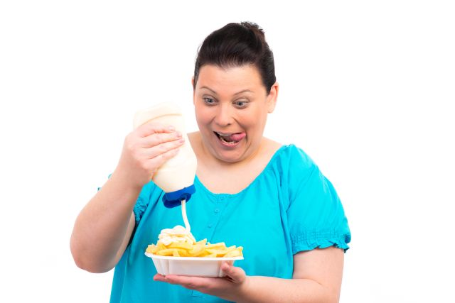 füllige Frau macht sich Mayo auf Pommes