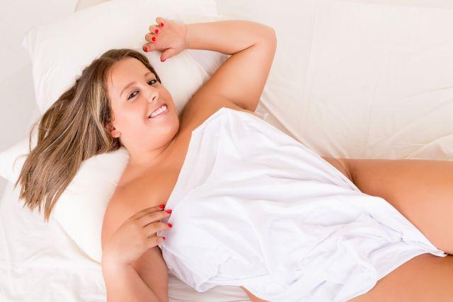 Dicke nackte Frau posiert im Bett
