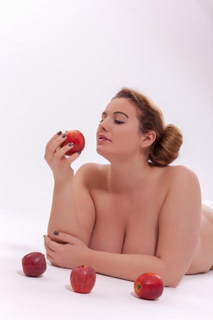 mollige Frau posiert nackt mit Äpfeln