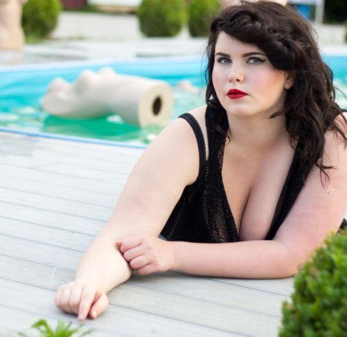 füllige Frau in schwarzem Badeanzug am Pool