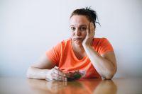 Frau stochert lustlos in Salatschüssel rum
