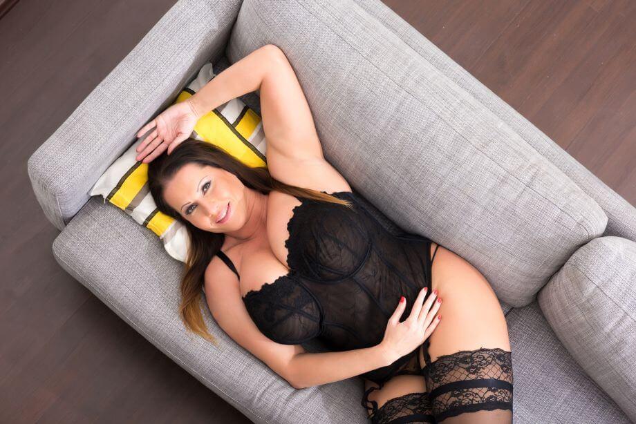Füllige Frau in schwarzem Spitzendessous liegt auf dem Sofa