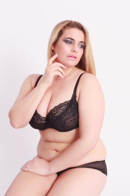 füllige Frau posiert in Dessous für Kamera