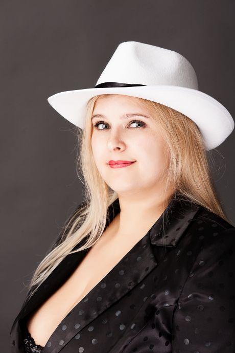 mollige Blondine mit einem weißen Hut auf dem Kopf
