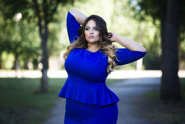 mollige Frau posiert in blauen Kleid für Kamera