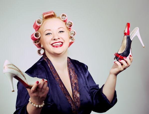 im 50s Look geschminkte Frau mit Lockenwicklern und Morgendmantel hält 2 verschiedene Pumps hoch