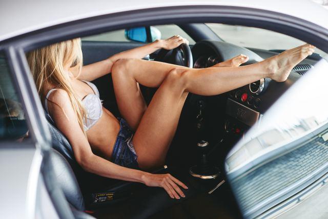 Frau in sexy Kleidung räkelt sich in Auto