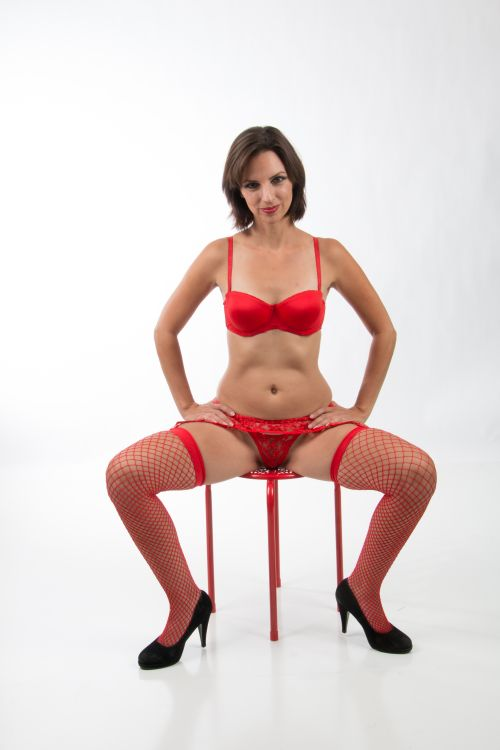sexy Adelaide Milf sitting on a chair in red lingerie