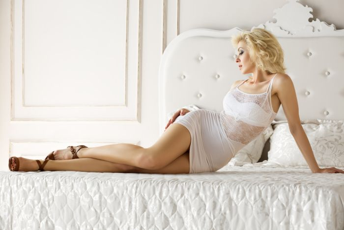 hot mature blond in lacy white dress on the bed