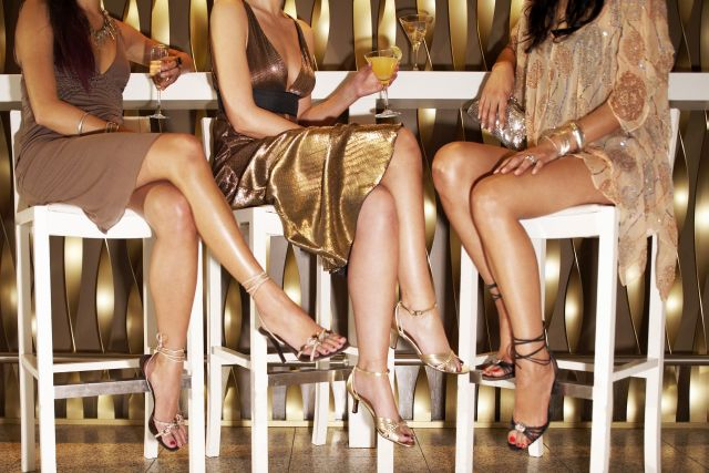Three sexy cougar women sitting in a bar