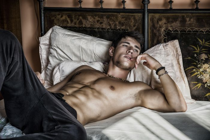 young sexy man lying in bed half naked
