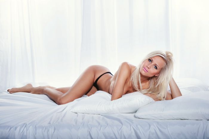 attractive blonde milf lying on the bed topless