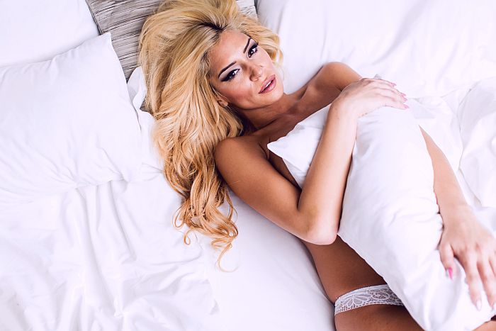 A radiant blonde lying on the bed covered by a pillow