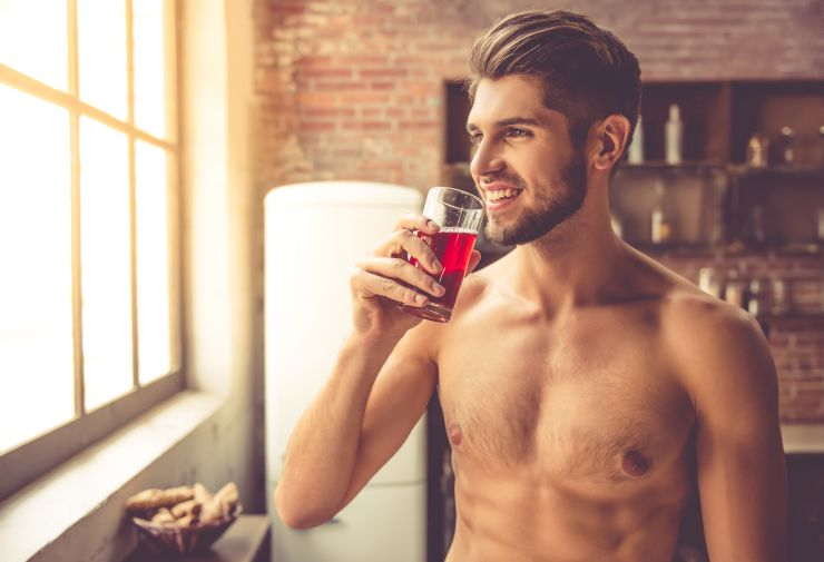 Sexy young man drinking in the kitchen