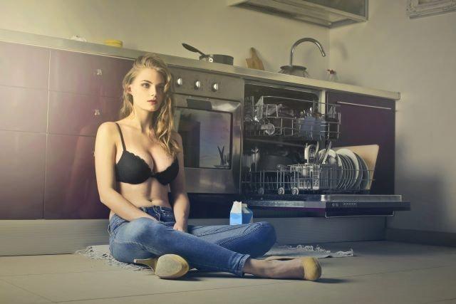 Sexy Frau sitzend mit Abwasch in Küche erschöpft