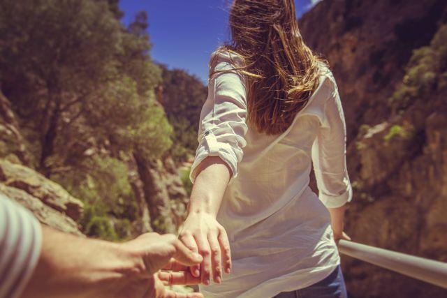 Frau zieht Mann hinter sich in den Bergen