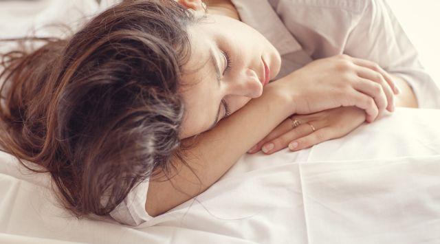 Frau liegt müde im Bett