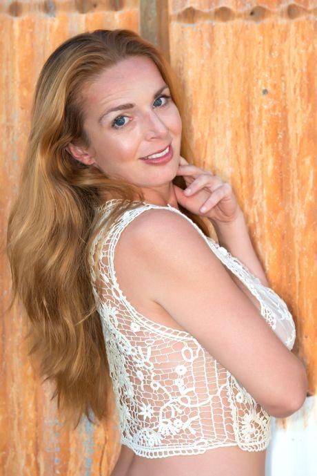 Reife attraktive Frau mit langen Haaren lächelt in die Kamera