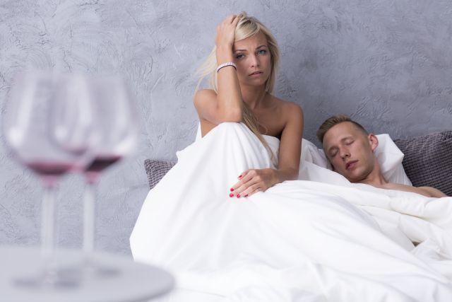 Paar im Bett mit Kater und 2 leere Weingläser im Vordergrund.