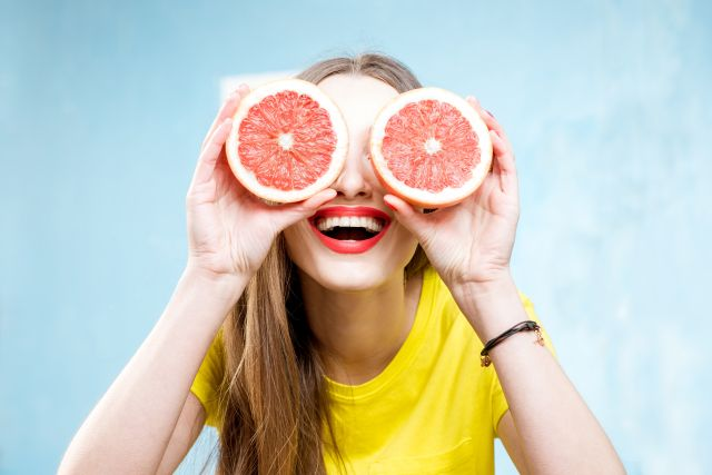 Junge Frau hlt sich Grapefruit vor die Augen