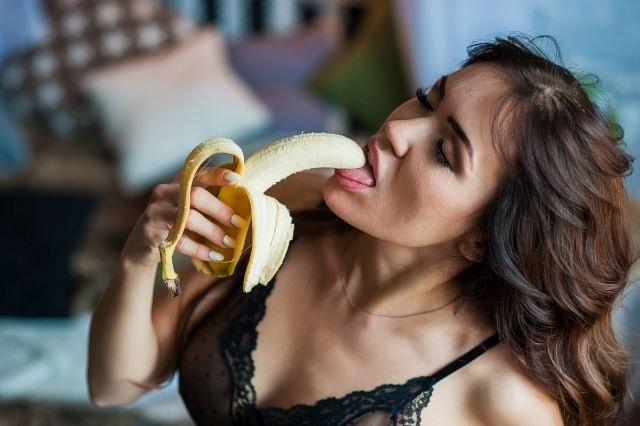 Frau nimmt Banane fast in den Mund