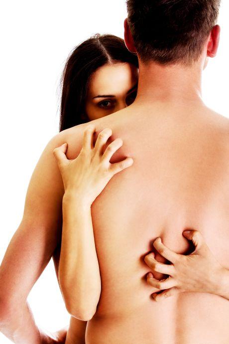 Nackte Frau schaut geheimnisvoll über die Schulter des Mannes