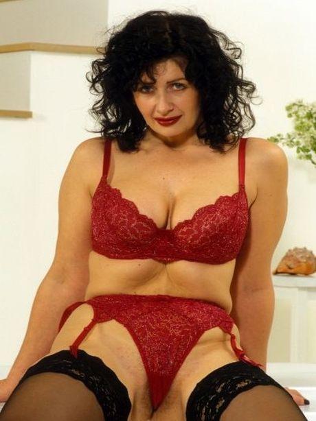 Reife Frau mit roter Wäsche