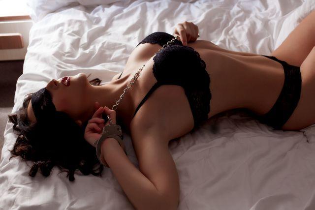Frau in Handschellen im Bett mit verbundenen Augen in Dessous
