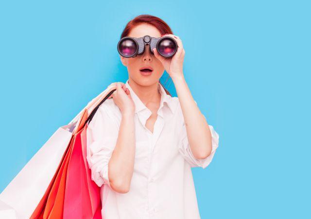 Frau mit Einkaufstüten schaut ins Fernglas