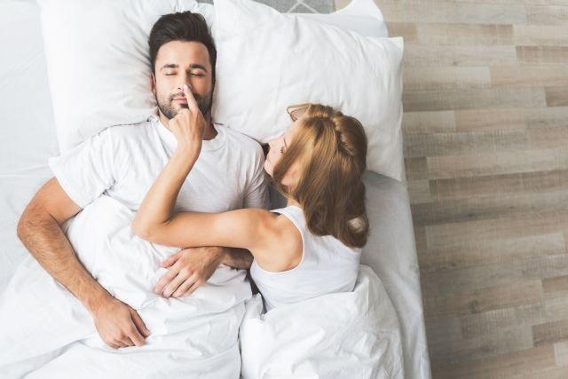 Mann täuscht vor zu schlafen und Frau fasst an seine Nase