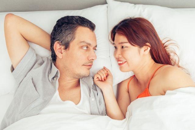 Paar liegt im Bett und redet