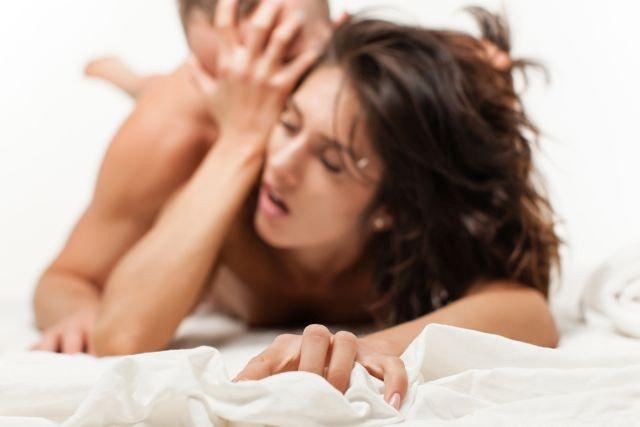 Frau beim Orgasmus im Bett mit Partner