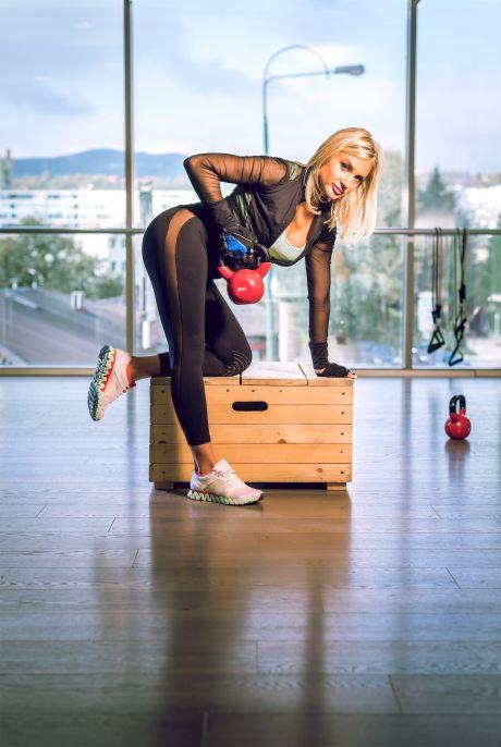 blonde MILF im Fitnessstudio mit einer Kettlebell