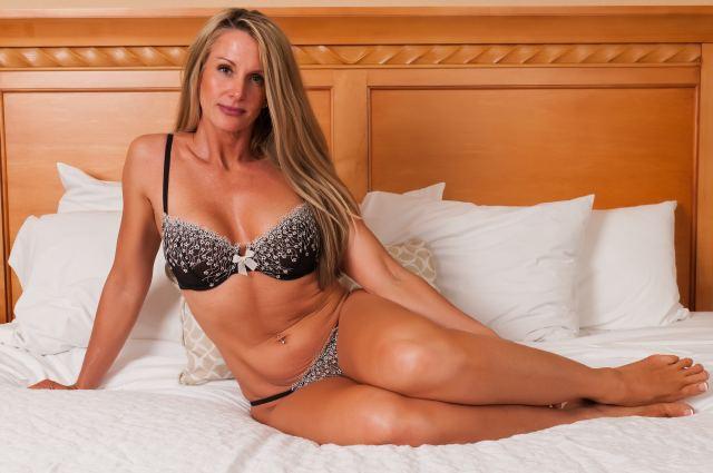 reife Blondine liegt auf Bett