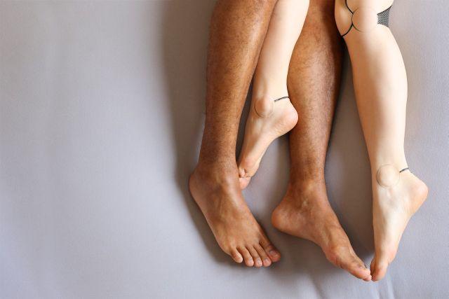 Beine von Frau und Mann im Bett