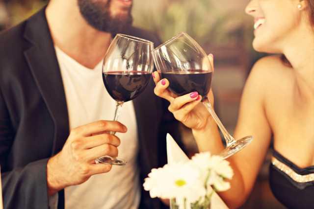 Paar stoßt im Restaurant mit einem Glas Wein an