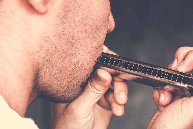 Mann spielt auf Mundharmonika