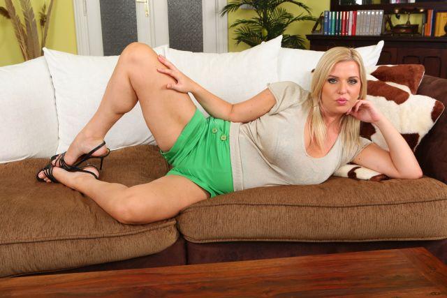 sexy reife Blondine in grünen Shorts auf einer Couch
