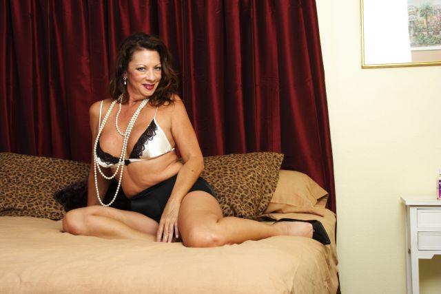 Reife attraktive Dame liegt in Dessous auf dem Bett