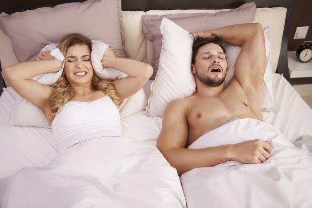 Mann schnarcht im Bett, Frau hält sich die Ohren zu