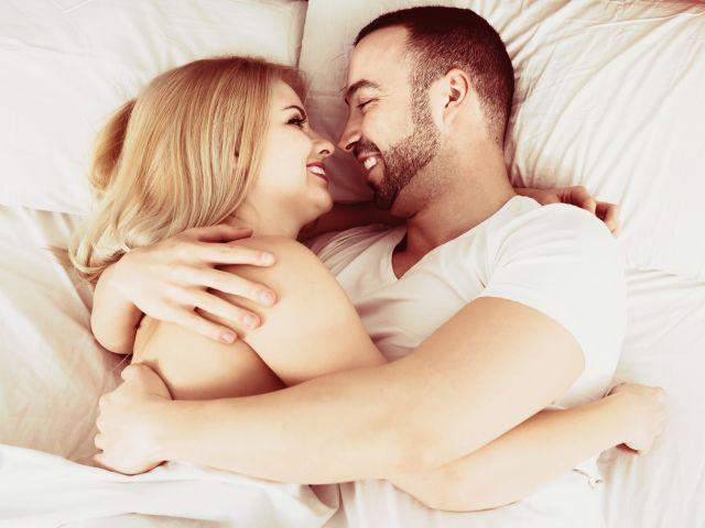 Frau und Mann im Bett schauen sich verliebt an