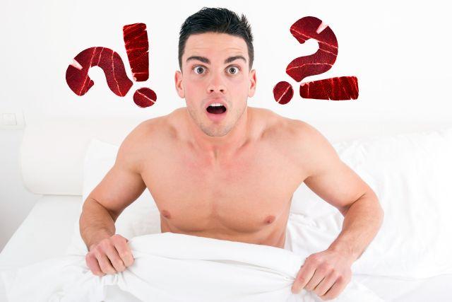 Junger Mann schaut überrascht im Bett