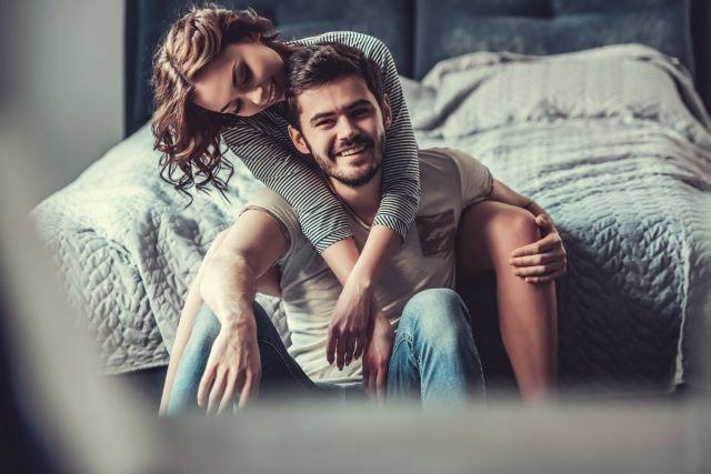 Glückliches Paar sitzend am Bett