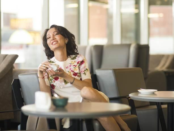 Frau sitzt mit Kaffeetasse in Restaurant