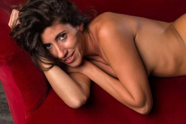 nackte Frau posiert auf rotem Sofa