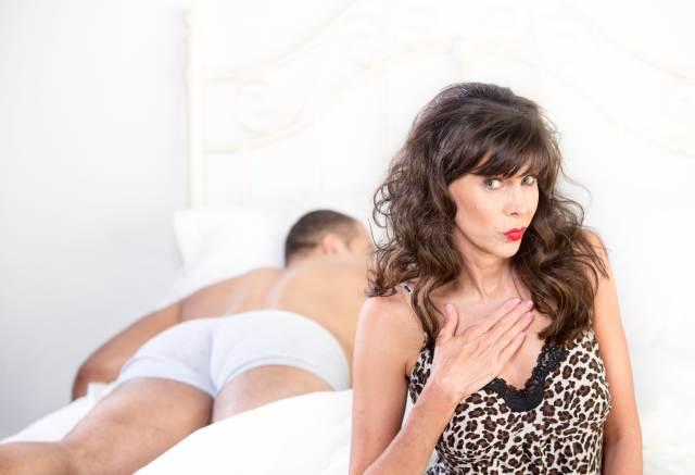 Reife Frau, hinter der ein Mann im Bett liegt