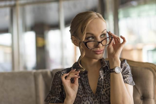 kesse Blondine schaut über den Rand ihrer Brille